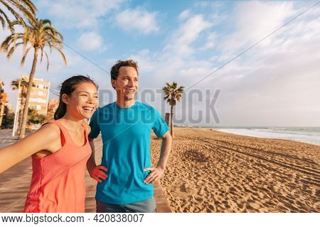 Happy healthy couple on beach run outside in Barcelona morning smiling. Young Asian woman and Caucasian runner man jogging. Active lifestyle people runners training looking at view.