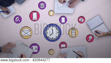 Composition of online digital icons over people writing in meeting on pink background. global online business and digital interface concept digitally generated image.