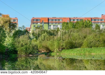 Lake On The Background Of Multi-storey City Houses. Trees Are Reflected In The Water, Ducks Are Swim