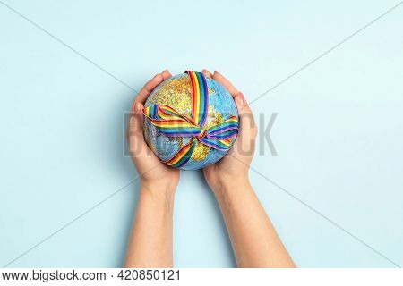 Female Hands Holding Globe With Lgbt Rainbow Ribbon On Blue Background. Lgbt Community. Homosexual P