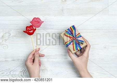 Female Hands Hold A Gift Box With Rainbow Lgbt Ribbon Nd Pair Of Decorative Lips On A Light Wooden T