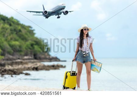 Asia Women Traveler Holding Yellow Luggage Walking And Holding Map Check In Smart Phone On The Beach