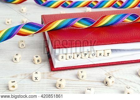 Word Support Written In Wooden Blocks In Red Notebook With Rainbow Lgbt Ribbon On Wooden Table. Lgbt