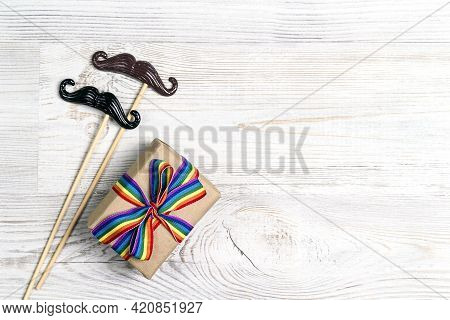 Gift Box With Rainbow Lgbt Ribbon And Pair Of Decorative Mustache On A Light Wooden Background. Homo