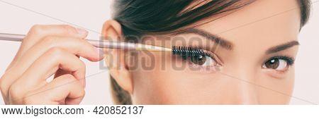 Beauty eyes lash lift. Eye makeup Asian woman applying mascara on eyelashes with make-up brush panoramic banner. Closeup of chinese eyes.