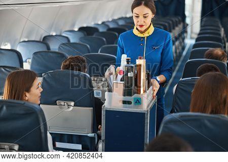 Cabin Attendant Leading Trolley Cart Through Plane Aisle