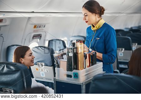 Woman On Plane Addressing Flight Attendant With Food Trolley