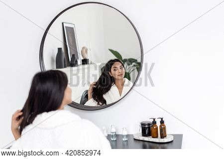 Concept Of Natural Beauty And Haircare Treatment At Home. Young Asian Woman In Bathrobe Sitting Behi