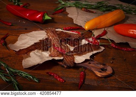 Jejerky Meat On Craft Paper And Spices On Brown Wooden Background. Ingredients For Cooking Meat Snac