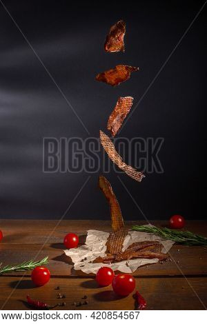 Food Levitation. Flying Meat Jerky In Front Of Dark Background. Dried Meat Snacks, Red Cherry Tomato
