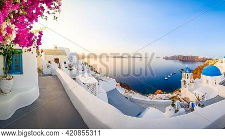 Traditional Greek Village Oia Of Santorini, With Blue Domes Against Aegan Sea And Caldera With Flowe