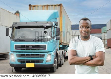 Professional Truck Driver Standing Arm Folded Smiling In Front Of The Semi Truck Container Yard. Afr