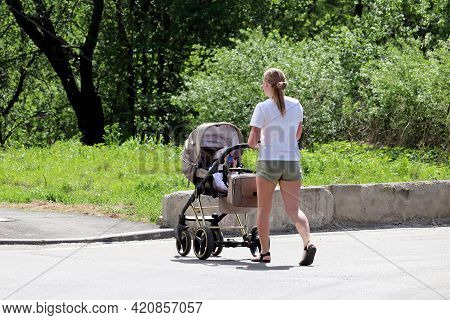 Woman In Summer Shorts With A Baby Stroller Crossing The City Street. Concept Of Motherhood, Walking