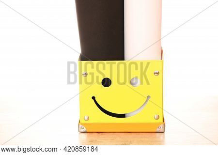 Yellow Paper Box With Multi-colored Background For Photographing. Bright Box For Documents On The Ta