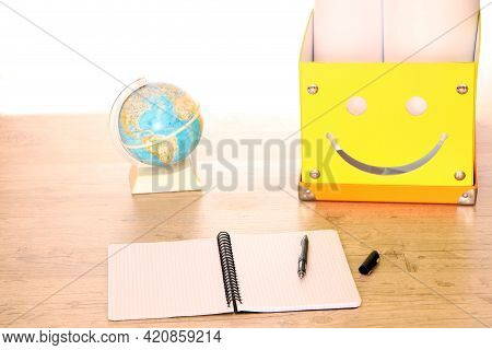 In The Office There Is A Yellow Box With Documents And A Globe On The Desktop. Classroom Teacher's D