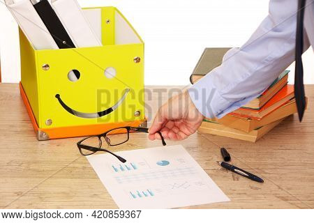 The Hand Of A Businessman Puts Glasses On The Work Table In The Office. A Student With Glasses In Th