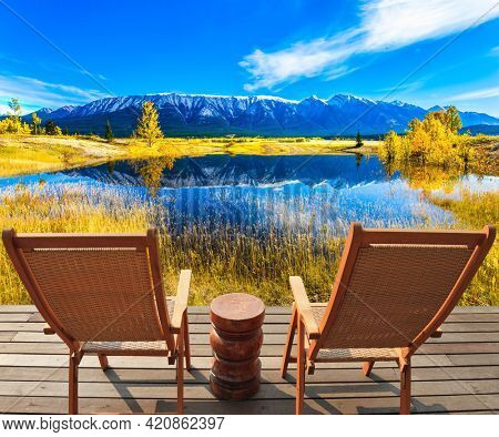 Indian Summer in the Rockies. Rocky Mountains are reflected in the turquoise smooth water of Lake Abraham. Concept of active and ecological tourism