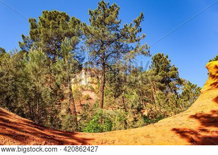 Bizarre ocher rocks. Provence, France. The village of Roussillon. Walk along the most beautiful red-yellow-orange route. The rocks are covered with forest. Sunny and warm day