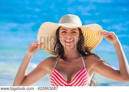 Smiling Woman wearing bikini swimwear and sunhat on sea beach