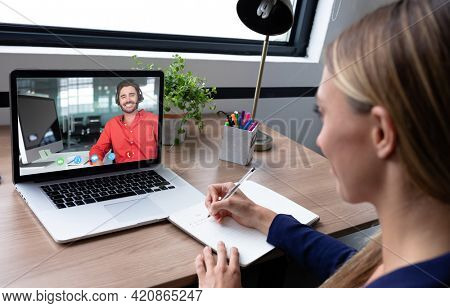 Caucasian woman sitting at desk having video call with coworker. online meeting, working in isolation during quarantine lockdown.