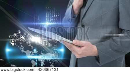 Composition of digital icons over caucasian businessman with tablet. global business, finance and networking concept digitally generated image.