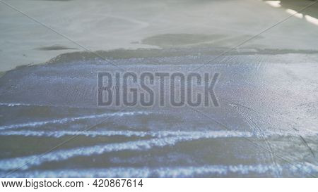 Priming The Floor In A Large Room. Worker Is Preparing The Floor With Adhesive Before Mounting The P
