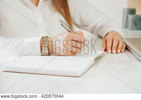 Young Womans Hands Holding Pen And Writing. Close Up Of Ladys Hand Writing In Notepad Placed On Desk