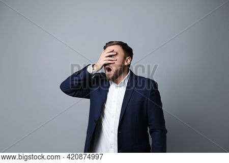 Young Businessman Feeling Fear On Grey Background