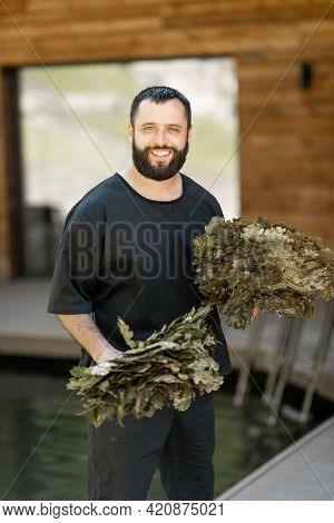 A Portrait Of The Bathhouse Attendant With Oak Broom For The Bath. Cheerful Male Personal In Spa.