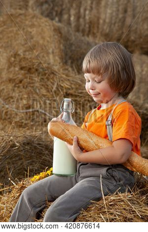 Little boy drink milk and eat a loaf of bread on a haystack in a village at sunset. Healthy childhood in harmony with nature