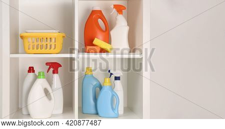 Shelving Unit With Different Cleaning Supplies And Tools Near White Wall