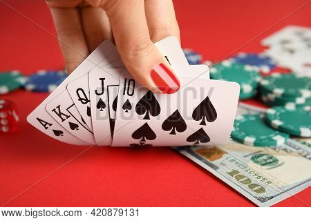 Woman Holding Playing Cards With Royal Flush Combination At Red Table, Closeup