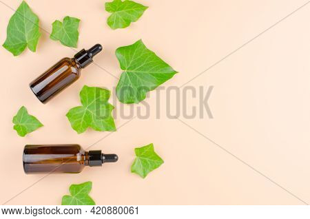 Two Brown Bottles With Oils And Ivy Leaves On A Beige Background With A Place For An Advertising Dis