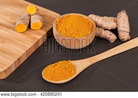 Turmeric - Curcuma Longa Root And Turmeric Powder; Photo On Dark Background.