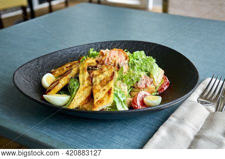 Fresh Caesar Salad With Chicken In A Black Bowl On The Veranda Of The Restaurant