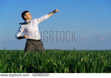 businessman posing in a field, he goes in for sports and does strikes like martial arts or superman, green grass and blue sky as background