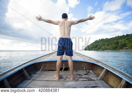 View Of Man In Swimsuit Enjoying On Thai Traditional Longtail Boat Over Beautiful Mountain And Ocean