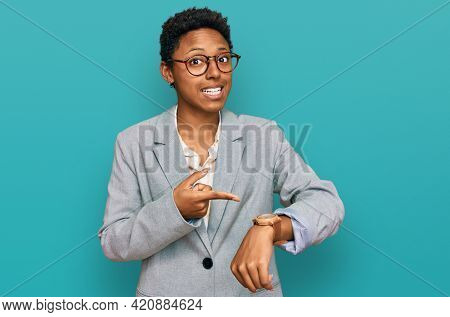 Young african american woman wearing business clothes in hurry pointing to watch time, impatience, upset and angry for deadline delay