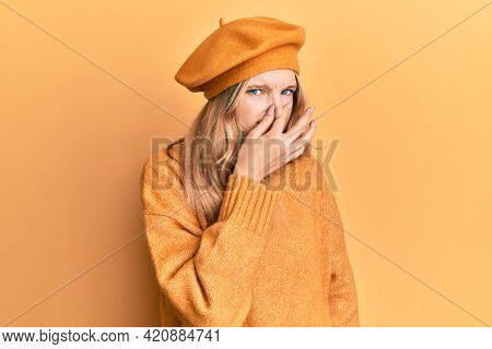 Beautiful young caucasian girl wearing french look with beret smelling something stinky and disgusting, intolerable smell, holding breath with fingers on nose. bad smell