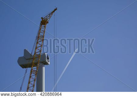 An Passenger Aircraft Is Drawing Contrails Behind A Wind Turbine Under Construction