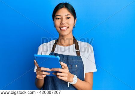 Young chinese woman wearing cook apron using touchpad smiling with a happy and cool smile on face. showing teeth.