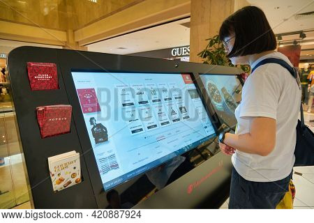 SINGAPORE - CIRCA JANUARY, 2020: woman use interactive touch screen kiosk at Nge Ann City shopping center.