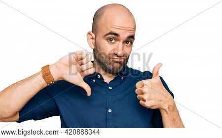 Young hispanic man wearing casual clothes doing thumbs up and down, disagreement and agreement expression. crazy conflict