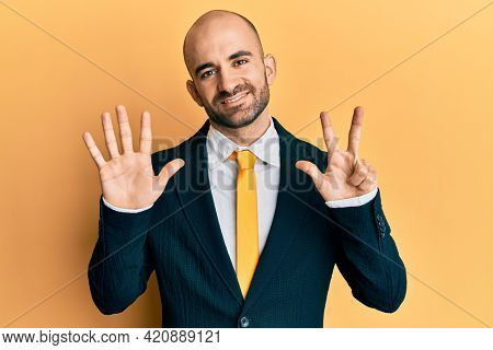 Young hispanic man wearing business suit and tie showing and pointing up with fingers number eight while smiling confident and happy.