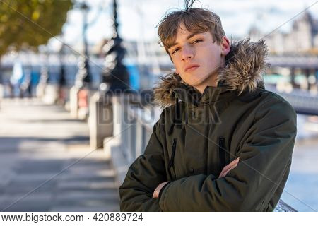Young adult male boy teenager outside in sunshine wearing a hooded parka coat in an urban city