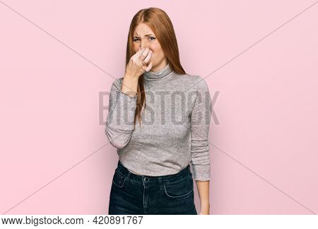 Young irish woman wearing casual clothes smelling something stinky and disgusting, intolerable smell, holding breath with fingers on nose. bad smell