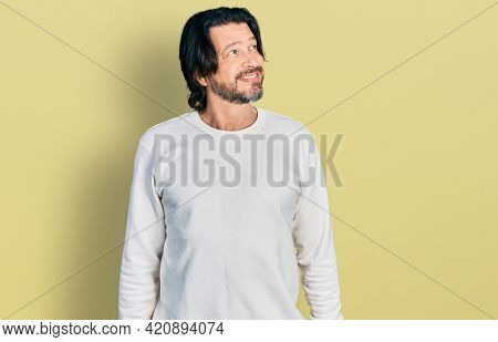 Middle age caucasian man wearing casual clothes smiling looking to the side and staring away thinking.