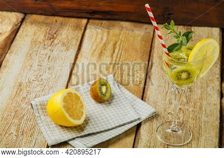 Cocktail With Kiwi Mint And Lemon In A Glass On A Wooden Table Next To Lemon And Kiwi On A Napkin.