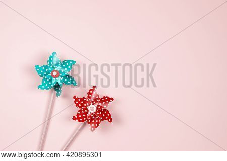 Two Colorful Windmill Pinwheels On Pastel Pink Background. Top View