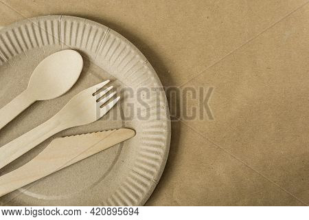 Disposable Wooden Cutlery: Spoon, Fork, Knife On A Paper Plate. Disposable Tableware Made Of Recycla